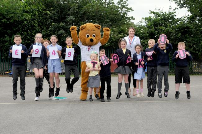 Pupils at Darnhall Primary School jump for joy with St Luke's mascot, Luke the bear, after raising £949 for the hospice