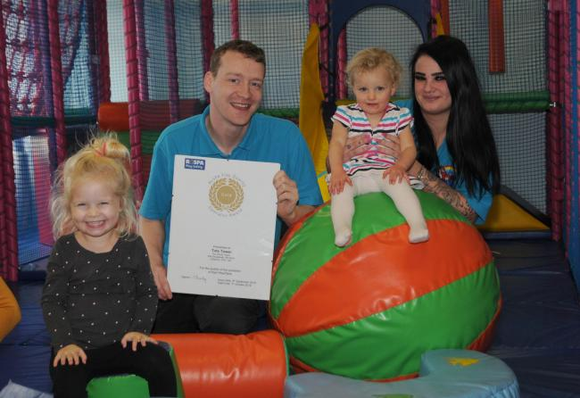 Tots Tower director Andy Webster with the RoSPA gold award and staff member Ellie Worthington watch Olivia Grannell and Eleanor Kettle having fun