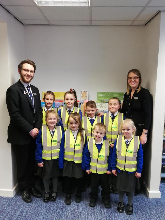 Specsavers James Barrett, optical assistant and Jackie Hickson, practice manager present high visibility vests to pupils from High Street Primary School