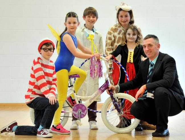 Pupils in their World Book Day costumes try out the bike, watched by principal Andrew Ross