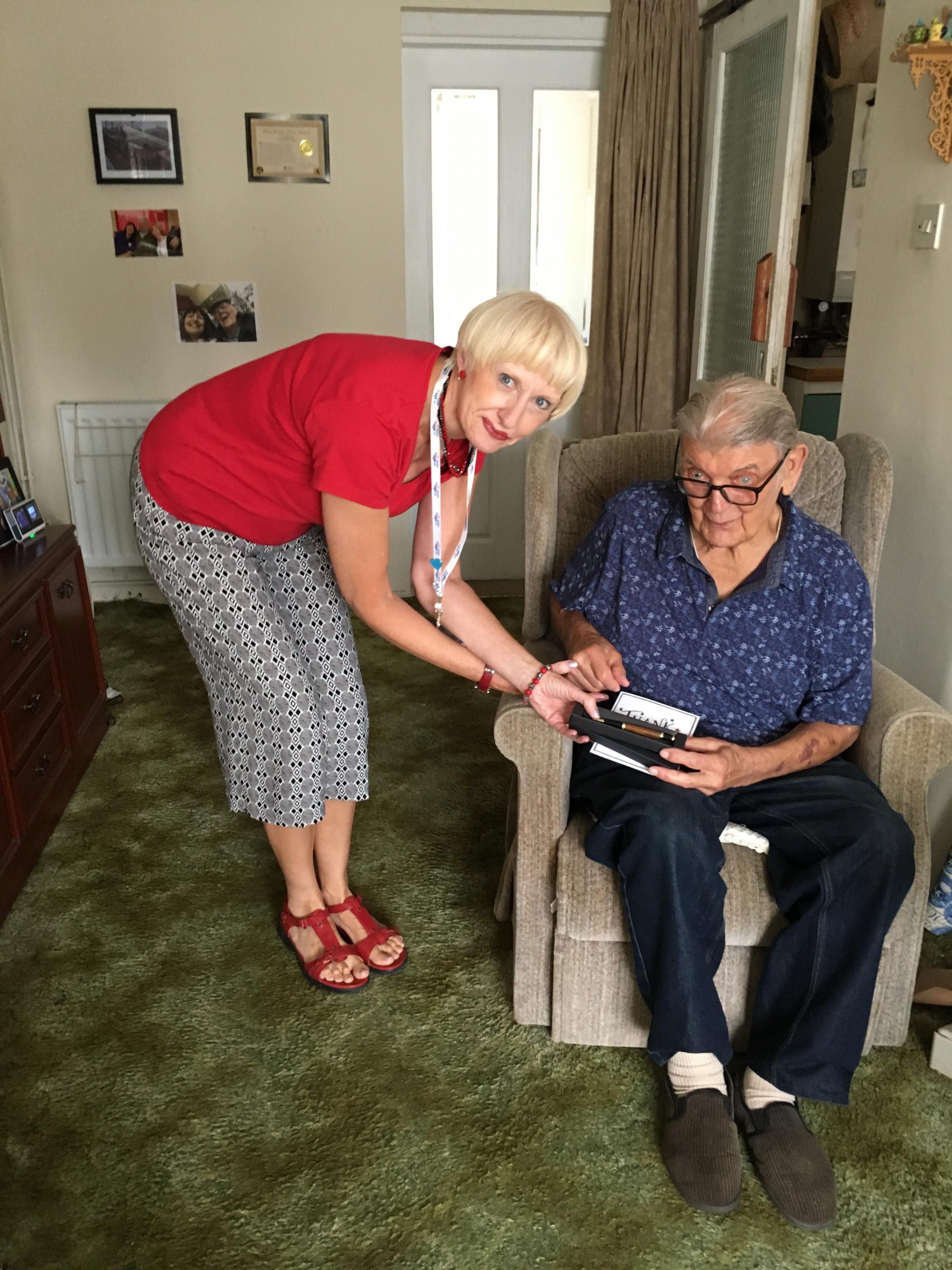 Tracy Etherington, falls prevention co-ordinator for Age UK Cheshire, presents an individually created handmade pen to George Blease
