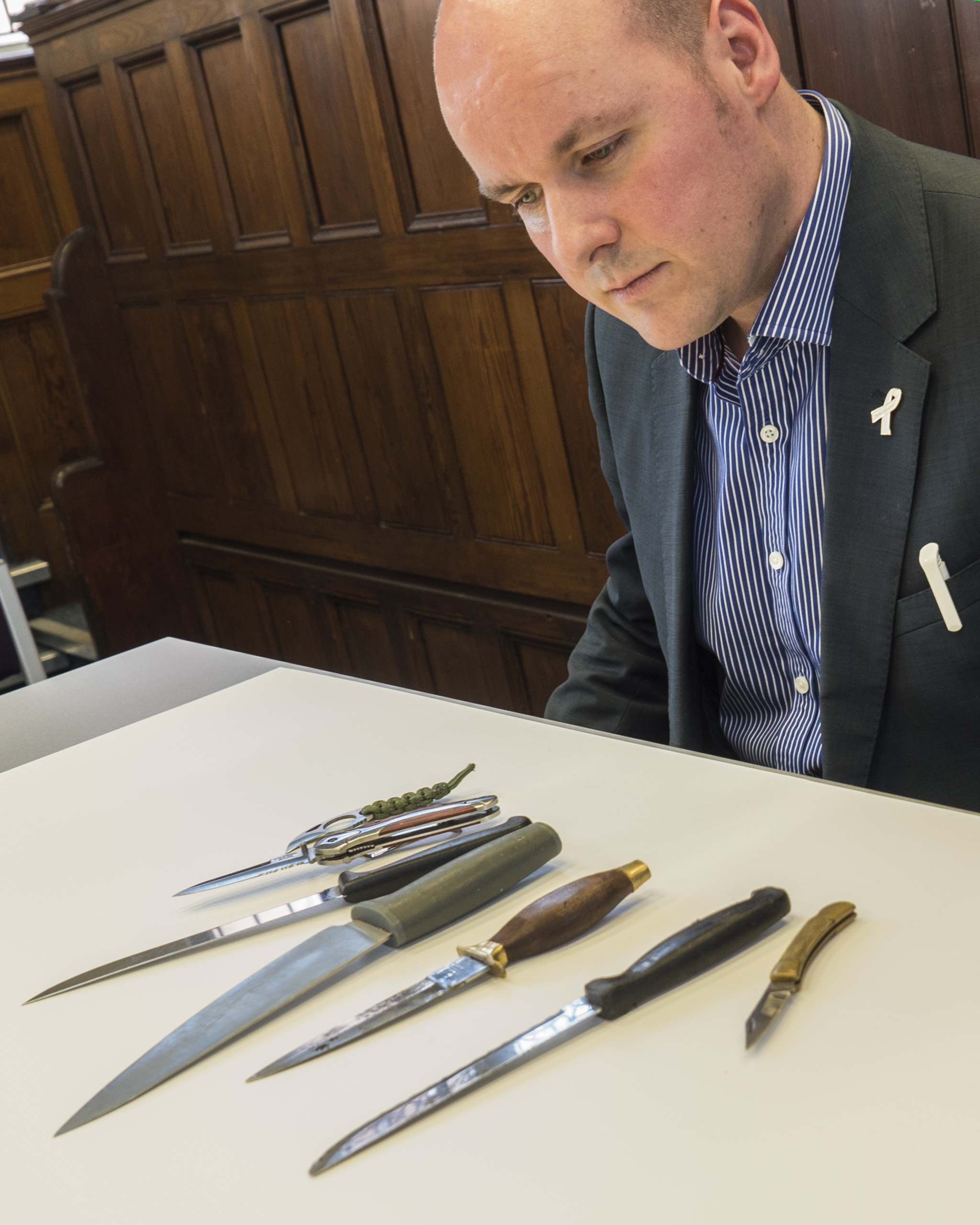David Keane examining seized knives