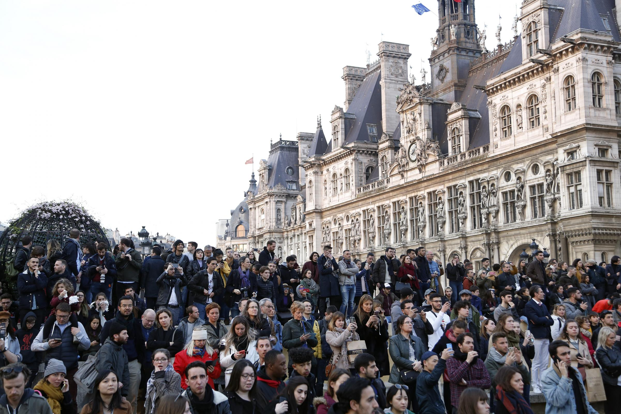 People watch as flames and smoke rise from Notre Dame Cathedral