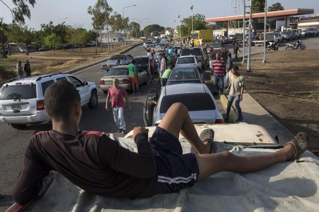 People line the street with their vehicles as they wait to fill up at a fuel station in Cabimas, Venezuela