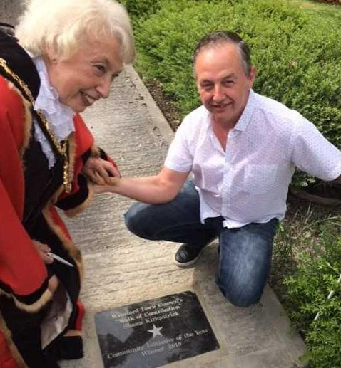 Last year's town mayor Cllr Gina Lewis honours fundraiser Shaun Kirkpatrick setting his name in stone on Winsford's Walk of Contribution